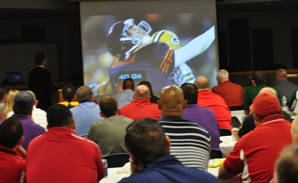 Coaches watch a video that details the severity of injury that can occur from head-to-head contact in football.