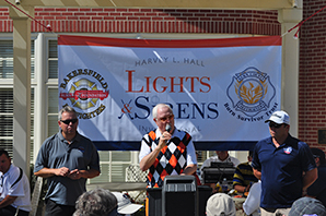 Harvey L. Hall joins Trever Martinusen and Derek Robinson in welcoming golfers to the 5th Annual Lights & Sirens Invitational.  The event has been re-named in his honor, for his decades of burn survivor support.